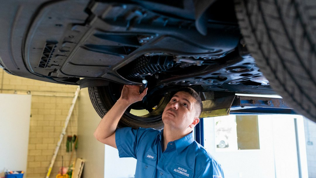 Mechanic inspecting underside of a vehicle